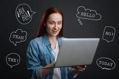 Blogger famoso que guarda um portátil e que lê comentários positivos imagens de stock royalty free