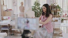 Blogger femenino bonito joven del diseñador de moda comunicar con sus seguidores en lugar de trabajo de costura atmosférico visua almacen de metraje de vídeo