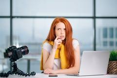 Blogger femenino con el ordenador portátil que piensa en un nuevo tema para el blog video Imagen de archivo libre de regalías