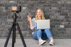 Blogger femenino rubio lindo con vídeo de la grabación del ordenador portátil Imagen de archivo