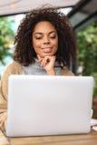 Blogger femenino sonriente que se sienta delante del ordenador portátil Fotografía de archivo