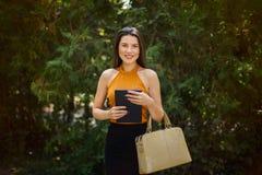 Blogger, femme d'affaires avec le comprimé et sac dans des mains sur la nature photos libres de droits