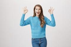 Blogger femminile attraente stupito ed eccitato che mostra segno giusto con entrambe le mani che ritengono grandi e che esprimono Fotografia Stock Libera da Diritti