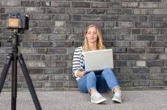 Blogger femminile biondo sveglio con il video della registrazione del computer portatile Fotografie Stock Libere da Diritti