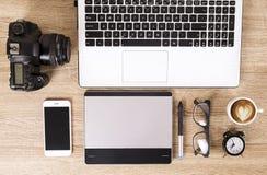 Blogger/fotógrafo/ele da foto tabela típica do espaço de escritórios do ` s do especialista com portátil, a tela vazia, o copo de fotografia de stock