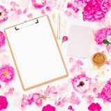 Blogger of freelancer composition. Workspace with clipboard, notebook, pen and pink roses on white background. Flat lay, top view. Stock Photography