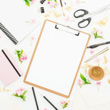 Blogger or freelancer workspace with clipboard, notebook, flowers and accessories on white background. Flat lay, top view. Blogger or freelancer workspace with stock photos