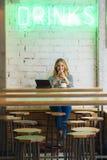 Blogger gai de femme travaillant avec la technologie dans un cafétéria Photo libre de droits