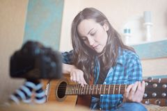 Blogger girl records on DSLR camera tutorial vlog for playing acoustic guitar.  Royalty Free Stock Photo