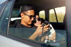 Blogger in glasses showing photos to his girlfriend on professional camera on road trip. Man photographer reviewing royalty free stock photos