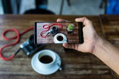 Blogger hand holding smart phone taking photo of coffee and camera on table. Blogger hand holding smart phone taking photo of coffee and camera on table royalty free stock images