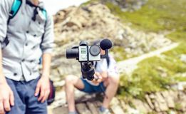 Blogger holding camera on monopod in mountains. Blogger holding camera on monopod, filming in Fagaras Mountains. Close-up shot. Place for text. Romania royalty free stock images