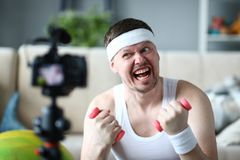 Blogger Holding Dumbbell in Hands for Exercise. Man with Funny Face Practice Fitness in Apartment. Male Recording Fitness Training on Digital Camera for Sport stock photo