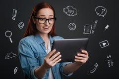 Blogger impresso que olha a tela ao estar com uma tabuleta moderna foto de stock