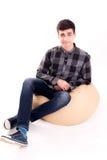 Blogger joven en la silla suave que hace la cara divertida aislada Imagen de archivo