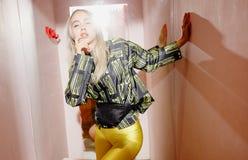 Blogger junges M?dchen der Mode gekleidet in einer stilvollen schwarzen und gelben Jacke und gelben Haltungen der kurzen Hosen in lizenzfreie stockbilder