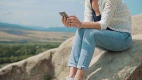 Blogger lindo de la muchacha que se sienta en una piedra contra el cielo, el valle y las montañas En contacto con sus suscriptore almacen de video
