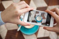 Blogger macht Fotos des Kaffees auf Tabelle im Café Lizenzfreie Stockfotos