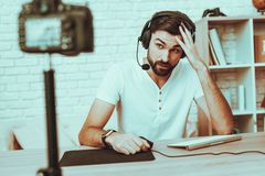 Blogger playing a video game on computer. Blogger Makes a Video. Blogger is Gamer. Blogger is Young Beard Man. Camera Shoots a Video. Man in Headphones Playing a royalty free stock photos