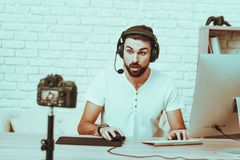Blogger playing a video game on computer. Blogger Makes a Video. Blogger is Gamer. Blogger is Young Beard Man. Camera Shoots a Video. Man in Headphones Playing a royalty free stock image