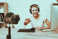 Blogger playing a video game on computer. Blogger Makes a Video. Blogger is Gamer. Blogger is Smiling Woman. Camera Shoots a Video. Woman in Headphones Playing a royalty free stock photo
