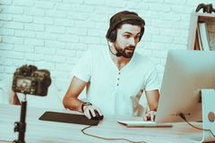 Blogger playing a video game on computer. Blogger Makes a Video. Blogger is Gamer. Blogger is Young Beard Man. Camera Shoots a Video. Man in Headphones Playing a stock photography