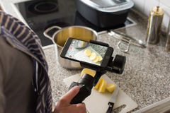 Blogger making smartphone video while cooking. Ostfildern, Germany - May 7, 2017: A female blogger is producing a video while cooking using the DJI Osmo Mobile royalty free stock photos