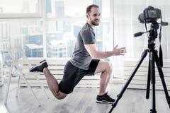 Blogger masculino alegre que muestra ejercicio simple Fotografía de archivo