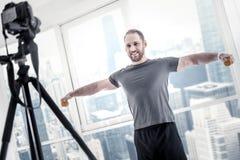 Blogger masculino alegre que se resuelve con pesas de gimnasia Fotos de archivo libres de regalías