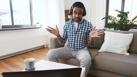 Blogger masculino con los auriculares videoblogging en casa almacen de metraje de vídeo