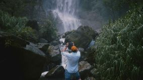 Blogger masculino feliz entusiasmado do curso da vista traseira que toma o vídeo do smartphone na cachoeira tropical cênico da se video estoque