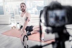 Blogger masculino positivo que toma el cuidado de músculos Imagen de archivo