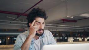 Blogger masculino subrayado usando el ordenador portátil en café metrajes
