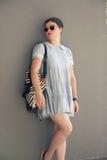 Blogger Mode der jungen Frau, der die graue Wand einfach aufwirft Stockfoto