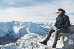 Blogger o freelancer joven que trabaja en un ordenador portátil en la cima del mundo Lanscape del invierno en día soleado imagen de archivo