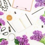 Blogger- oder Freiberuflerarbeitsplatz mit Klemmbrett, Notizbuch, Lippenstift, Niederlassungen der Flieder und Zubehör auf weißem Stockfotografie