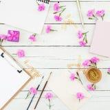 Blogger- oder Freiberuflerarbeitsplatz mit Klemmbrett, Notizbuch, rosa Blumen und Zubehör auf rustikalem hölzernem rustikalem Hin Stockfotos