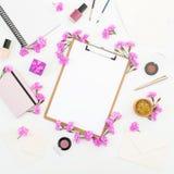 Blogger- oder Freiberuflerarbeitsplatz mit Klemmbrett, Notizbuch, rosa Blumen und Zubehör auf weißem Hintergrund Flache Lage, Dra Stockfotos