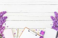 Blogger- oder Freiberuflerarbeitsplatz mit Klemmbrett, Notizbuch, Stift, Flieder, Kasten und den Blumenblättern auf hölzernem Hin Lizenzfreies Stockfoto