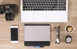 Blogger/photographe/lui de photo table typique de bureaux du ` s de spécialiste avec l'ordinateur portable, l'écran vide, la tass Images stock