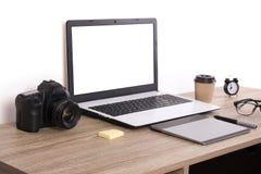 Blogger/photographe/lui de photo table typique de bureaux du ` s de spécialiste avec l'ordinateur portable, l'écran vide, la tass Photo libre de droits