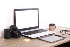 Blogger/photographe/lui de photo table typique de bureaux du ` s de spécialiste avec l'ordinateur portable, l'écran vide, la tass Photos stock