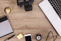 Blogger/photographe/lui de photo table typique de bureaux du ` s de spécialiste avec l'ordinateur portable, l'écran vide, la tass Photographie stock libre de droits