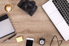 Blogger/photographe/lui de photo table typique de bureaux du ` s de spécialiste avec l'ordinateur portable, l'écran vide, la tass Image libre de droits