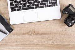 Blogger/photographe/lui de photo table typique de bureaux du ` s de spécialiste avec l'ordinateur portable, l'écran vide, la tass Images libres de droits