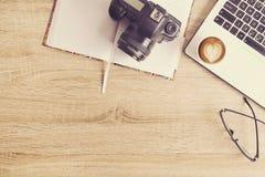 Blogger/photographe/lui de photo table typique de bureaux du ` s de spécialiste avec l'ordinateur portable, l'écran vide, la tass Photographie stock