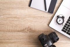 Blogger/photographe/lui de photo table typique de bureaux du ` s de spécialiste avec l'ordinateur portable, l'écran vide, la tass Photos libres de droits