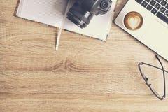 Blogger/photographe/lui de photo table typique de bureaux du ` s de spécialiste avec l'ordinateur portable, l'écran vide, la tass Image stock