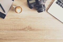 Blogger/photographe/lui de photo table typique de bureaux du ` s de spécialiste avec l'ordinateur portable, l'écran vide, la tass Photo stock