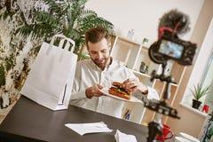 Blogger positivo do alimento do café da manhã saudável que guarda uma placa com sanduíche fresco ao gravar o vídeo novo para seu  imagens de stock